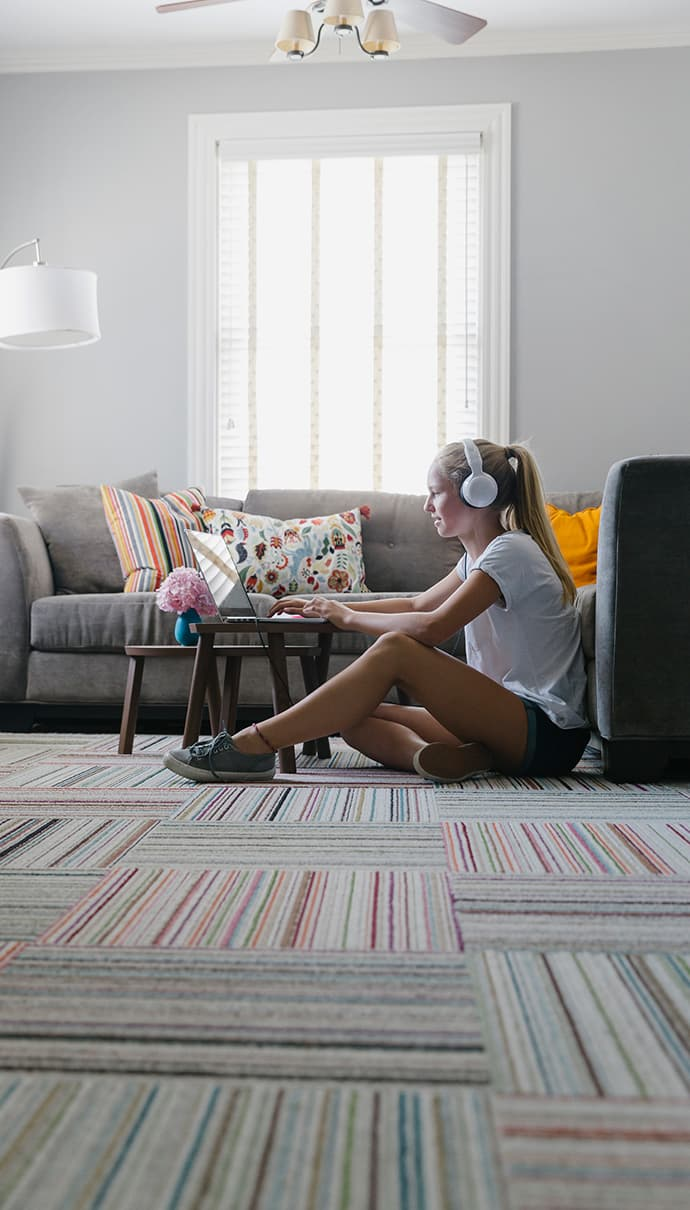 Girl siting on her floor using her laptop with headphone